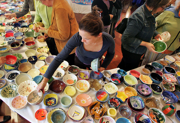 "Gloucester:  Laura Waxdal of Gloucester has trouble deciding what bowl to choose at the Open Door/Cape Ann Food Pantry's nineth annual Empty Bowl Dinner held at Cruiseport Thursday evening. After coming to the event for five years Waxdal says she has ""the best collection of bowls."" Mary Muckenhoupt/Gloucester Daily Times"