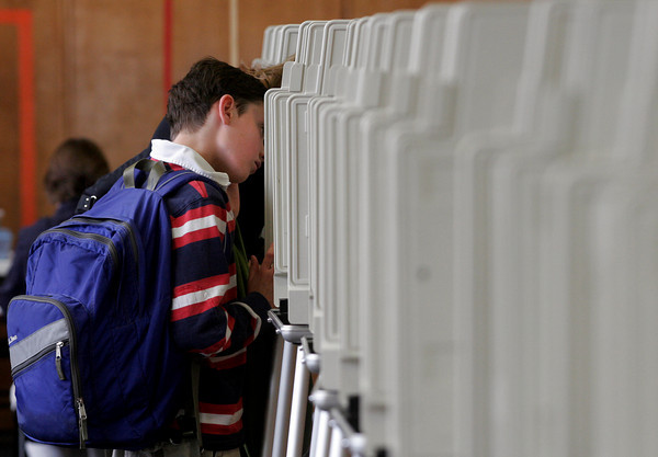 Manchester: Liam Setzer, 11, accompanies his mother, Julie Setzer, to the voting booth at Manchester Memorial Elementary School yesterday afternoon. Photo by Kate Glass/Gloucester Daily Times