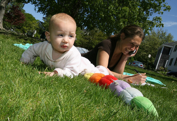 Manchester: Eva Jane Friz, 6 months, explores the grass at the Brook Street Playground while her mom, Cassi Friz, takes a business call on Thursday afternoon. The two were headed to Woodman's after their brief stop at the park. Photo by Kate Glass/Gloucester Daily Times