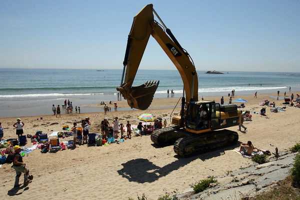 Manchester: David Milnes of Waterline Industries guides their construction equipment through beachgoers at Singing Beach in Manchester yesterday. The company has been making repairs to the seawall, which was damaged several years ago. Work is expected to be completed before Memorial Day weekend. Photo by Kate Glass/Gloucester Daily Times