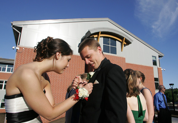 Manchester: Caroline Cummings puts a boutonniere on her date Yuri Klypka-Simpson in front of the Manchester Essex Regional High School before heading to their prom  Friday evening. The Manchester Essex prom was held at the Hellenic Community Center in Ipswich. Mary Muckenhoupt/Gloucester Daily Times