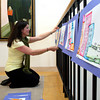 Gloucester: Courtney Richardson hangs art done by students from Veterans Memorial Elementary School at the Cape Ann Museum Thursday afternoon.  Richardson was getting the museum ready for the Gloucester Spring Arts Festival to be held Saturday at the Cape Ann Museum, Sawyer Free Library, Gloucester City Hall, Cape Ann Savings Bank and Art Haven. Mary Muckenhoupt/Gloucester Daily Times