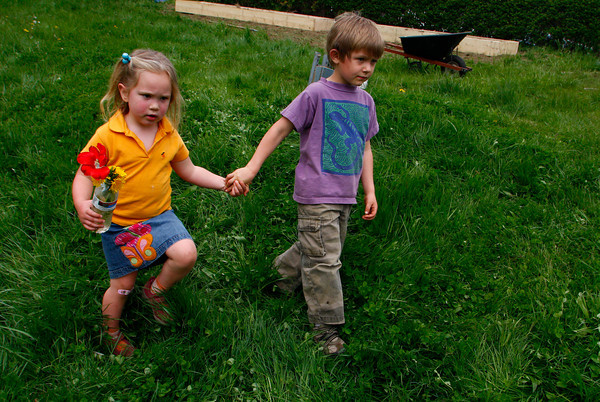 Gloucester: Thea Cunningham and Ian Buchanan walk hand in hand toward their parents who were gardening in front of the West parish Elementary School Saturday morning. Mary Muckenhoupt/Gloucester Daily Times