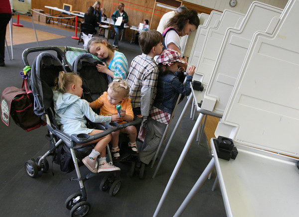 Manchester: Madeline Donnellan, 8, rests her head on the stroller while she and her siblings, Isabelle and Charlotte, both 3, and Owen and Madeline, both 8, wait for their mother, Vicki Donnellan, to vote at Manchester Memorial Elementary School yesterday afternoon. Photo by Kate Glass/Gloucester Daily Times