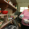 Gloucester: Marty Morgan removes several of the bowls for the Empty Bowl Dinner from the shelves of her pottery studio yesterday afternoon. Morgan glazes many bowls for the annual fundraiser for The Open Door, which is Thursday at Cruiseport from 4 to 8. Photo by Kate Glass/Gloucester Daily Times