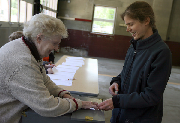 Essex: Gloria Story helps Amy Blondin cast her ballot in the Essex election yesterday. The ballot got stuck in the box, but eventually went through. Photo by Kate Glass/Gloucester Daily Times