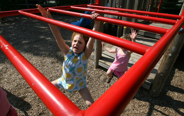 Manchester: Lily Iler, 4, of Wenham swings across the monkey bars at Masconomo Park on Wednesday afternoon. Iler also loved hanging upside down from the bars. Photo by Kate Glass/Gloucester Daily Times