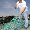 Gloucester: Sal Ciolino helps his friend, Sal Carollo (not shown), mend the nets for his boat, the Princess Elena, on the Jodrey State Fish Pier yesterday morning. The fishing vessel is out of the water for maintenance. Photo by Kate Glass/Gloucester Daily Times