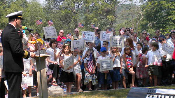 Rockport: Rockport Elementary School students hold the names of Rockport veterans who passed away this year during the town's Memorial Day ceremony yesterday. Photo by Gail McCarthy/Gloucester Daily Times