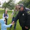 Gloucester: Simon Dixon shakes Gloucester Police Officer Mark Foote's hand after he helped a mother and her ducklings safely cross Grant Circle yesterday afternoon. Simon and his sister, Madelyne, and mom, Heidi, stopped when they saw the ducks trying to cross the road and wanted to help them cross. Photo by Kate Glass/Gloucester Daily Times