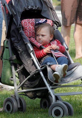 Gloucester: Teagan Dorothy Shank, 11 months, plays with an American flag during Gloucester's Memorial Day ceremony at Kent Circle yesterday morning. Photo by Kate Glass/Gloucester Daily Times