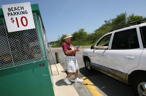 Gloucester: Ron Bielicki of Gloucester collects money for parking at Wingaersheek Beach yesterday afternoon. The city opened Wingaersheek, Good Harbor, and Stage Fort Park on Friday, though the parking rate is discounted until Memorial Day Weekend when regular rates go into effect. Photo by Kate Glass/Gloucester Daily Times