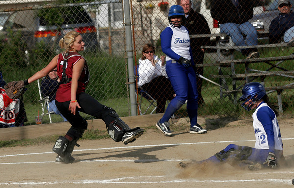 Gloucester: Gloucester catcher Addy Blakeley gets a late throw to home plate as Danvers' Caitlyn Ward slides safely across after hitting a home run at Burnham Field yesterday afternoon. Photo by Kate Glass/Gloucester Daily Times