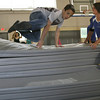 Gloucester: Jacob Wagner leaps over a pile of mats as MAC instructor Marette LeBoeuf keeps them steady during the obstacle course section of the MAC's enrichment program on Wednesday. Seventh grade students from O'Maley Middle School participating in the program. Photo by Kate Glass/Gloucester Daily Times