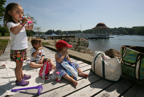 Manchester: Rose Groleau, 3, Charlie Groleau, 5, and Callie Brady, 2, enjoy a snack at Tuck's Point before returning to play in the sand yesterday morning. Photo by Kate Glass/Gloucester Daily Times