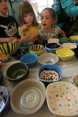Gloucester: Michael Newman, 8, and Olivia Newman, 6, both of Rockport, watch as Olive Sauder, 5, of Gloucester selects a bowl at the Open Door's 10th Annual Empty Bowl Dinner at Cruiseport last night. Michael selected a bowl he had made for the event. Photo by Kate Glass/Gloucester Daily Times