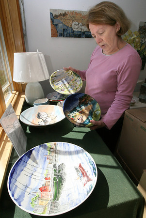 Gloucester: Marty Morgan displays several of the bowls up for auction at the Empty Bowl Dinner, including ones painted by Mark Lindsay, Kevin Ellis, Marilyn Swift, and Veronica Morgan. Photo by Kate Glass/Gloucester Daily Times