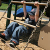 Essex: Jack Clarke smiles as he hangs from a chain ladder on the playground at Memorial Park in Essex on Thursday afternoon. Photo by Kate Glass/Gloucester Daily Times