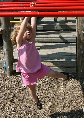Manchester: Tess Carpenter, 3, of Manchester swings across the monkey bars at Masconomo Park on Wednesday afternoon. Photo by Kate Glass/Gloucester Daily Times