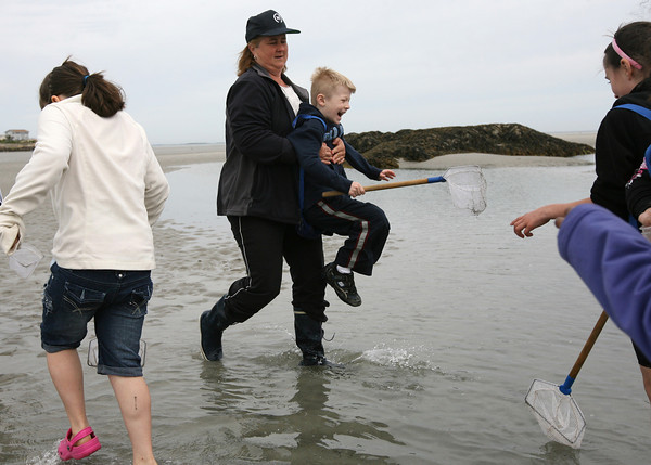 Gloucester: Jude Bowers laughs as Leslie Beaulieu carries him across the water so his shoes do not get wet as Mrs. McKechnie's second grade class from West Parish Elementary School explore tidal pools at Wingaersheek Beach yesterday morning. The students were exploring the relationships between living creatures and their habitat through a program sponsored by the Gloucester Education Foundation. Photo by Kate Glass/Gloucester Daily Times