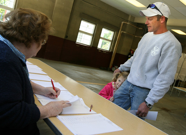 Essex: Hailey Rogers, 4, hides behind her father, Todd Rogers, as he votes in the Essex election at the Fire Station yesterday. Photo by Kate Glass/Gloucester Daily Times