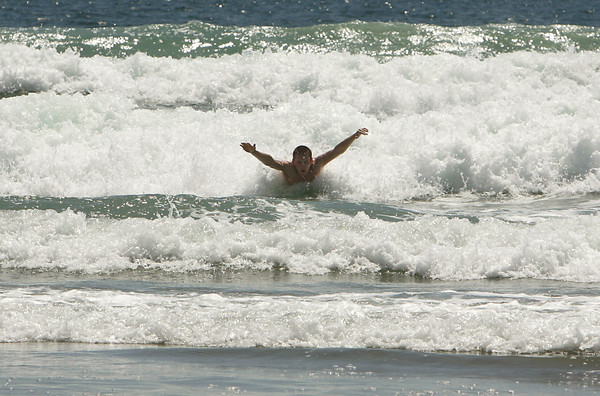 Gloucester: Chris Muise swims through a wave at Good Harbor Beach Thursday afternoon.  Muise said he is leaving for Georgia in a few weeks and wants to enjoy the cold ocean water while he can. Mary Muckenhoupt/Gloucester Daily Times