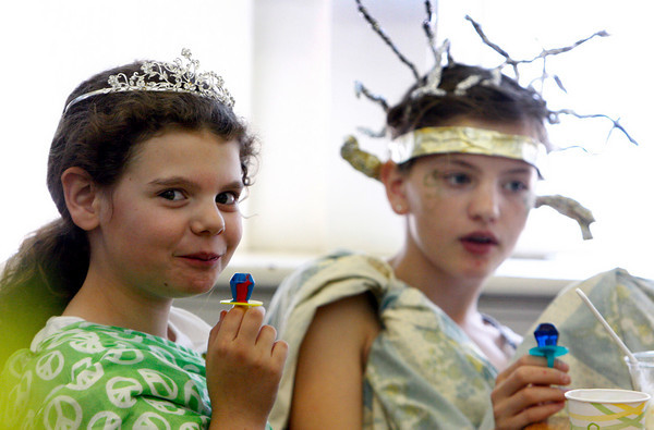Essex: Austin Pare, 9, enjoys her ring pop while attending the Gods and Goddesses Gala at the TOHP Burnham Library Saturday afternoon.  Pictured left is Sasha Ball, 12. Mary Muckenhoupt/Gloucester Daily Times