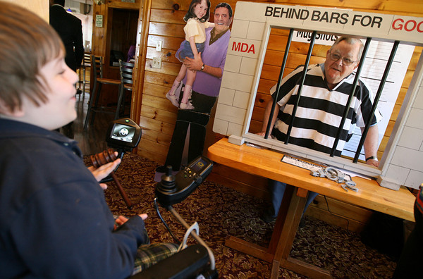 "Gloucester: Joseph Miller, 7, of Haverhill tells Jerry Skeen of Rockport that he is being arrested for having a big heart as he participates in the Muscular Dystrophy Association's Lock-Up fundraiser at Lobsta Land on Tuesday. Dozens of local business and civic leaders were ""locked up"" with a goal of raising $1,600 each as ""bail."" Miller was diagnosed with Spinal Muscular Atrophy Type 2, one of dozens of forms of MD, when he was 18 months old. Photo by Kate Glass/Gloucester Daily Times"