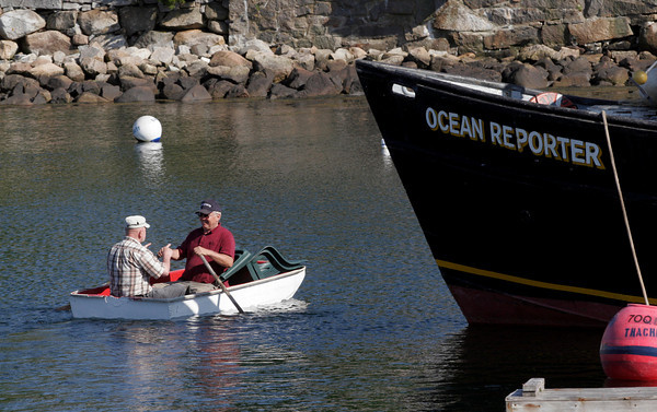Rockport: Bill Lee rows around his boat, the Ocean Reporter, with Larry Martin yesterday afternoon. The two set out chairs on one of the nearby floats. Photo by Kate Glass/Gloucester Daily Times