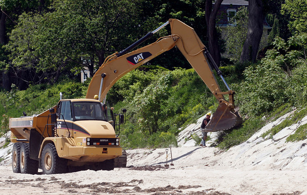Manchester: Employees of Waterline Industries finish up their repair work to the seawall at Singing Beach yesterday. They will shore up the culdesac today and expect all work to be completed for Memorial Day weekend. Photo by Kate Glass/Gloucester Daily Times