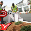 Gloucester: James Bobb, left, and Nate Gumprecht of Neokraft Signs install the sign for Olympia Sports yesterday afternoon, which is the next business scheduled to open at Gloucester Crossing. Photo by Kate Glass/Gloucester Daily Times