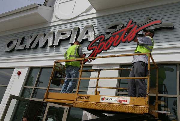 Gloucester: Nate Gumprecht and James Bobb of Neokraft Signs install the letters for Olympia Sports yesterday afternoon, which is the next business scheduled to open at Gloucester Crossing. Photo by Kate Glass/Gloucester Daily Times