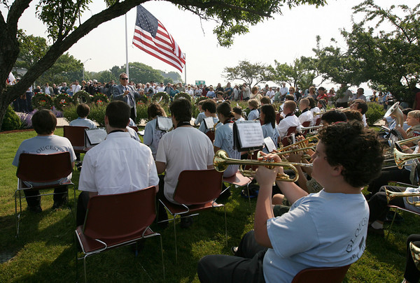 Gloucester: David Benjamin conducts the Gloucester City-Wide Band as they play the Star Spangled Banner during Gloucester's Memorial Day ceremony at Kent Circle yesterday morning. Photo by Kate Glass/Gloucester Daily Times