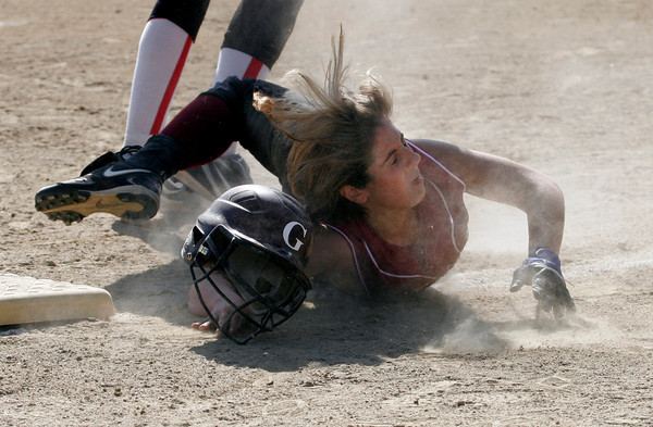Gloucester: Gloucester center fielder Sam Saputo loses her helmet as she dives back to third base while caught in a pickle during their game against Saugus at Burnham Field yesterday. Photo by Kate Glass/Gloucester Daily Times