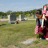 Gloucester: Megan Marchant, right, and Kathleen Guyer, both members of Gloucester High School ROTC, place flags on veterans' gravestones at Calvary Cemetery yesterday afternoon. The ROTC students place 1,500 flags throughout the cemetery every year in preparation for Memorial Day. Photo by Kate Glass/Gloucester Daily Times