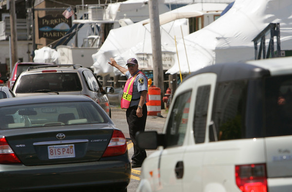 Gloucester: Gloucester police officer Ernie Curtis directs traffic at the Causeway in Essex Friday afternoom. The flaggers were removed from their job by the Massachusetts Department of Transportation after a confrentation with a motorist.  Mary Muckenhoupt/Gloucester Daily Times