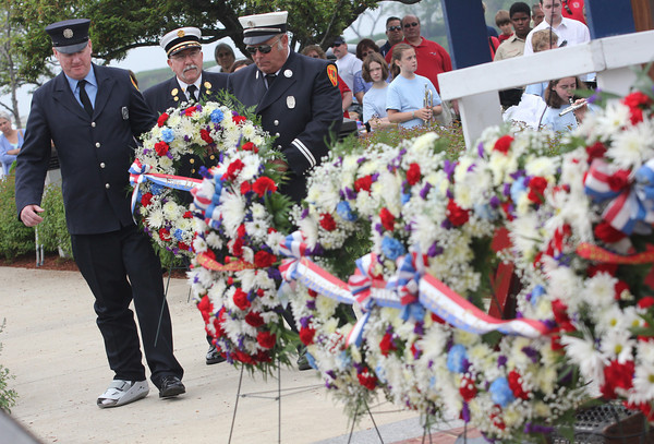 Gloucester Firefighter Dan Kennedy, Chief Phil Dench, and Captain Robert Parsons place a wreath at the base of the World War II Memorial during Gloucester's Memorial Day ceremony yesterday. Photo by Kate Glass/Gloucester Daily Times