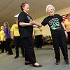 Joan Sikorski holds Kit Abrahamson's hand after the 104-year-old performed with the Cape Ann Seniorettes at Day by Day Adult Care Center. Kit broke two ribs in a recent fall, but is back on her feet again just three weeks out of rehabilitation at Seacoast. Photo by Kate Glass/Gloucester Daily Times