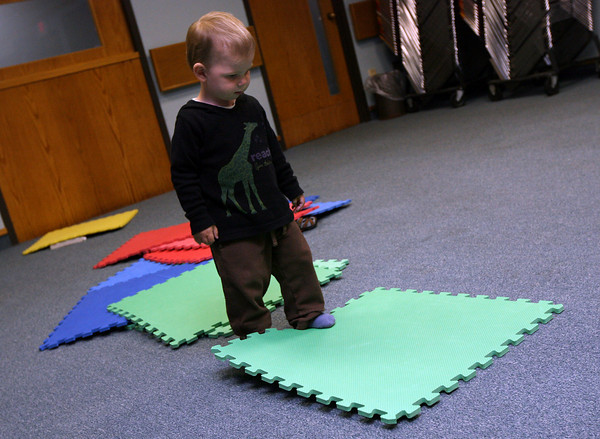 James Paine, 2, plays with puzzle mats in the Friend Room of the Sawyer Free Library while his mother, Clea, hangs student artwork for the Gloucester Public School District Citywide Arts Festival. Photo by Kate Glass/Gloucester Daily Times