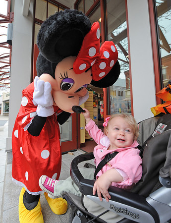 Gloucester: Mini Mouse gets her nose squeezed by Violet Kendell Lee 15 months as she looks back at her Grandmother Buffy Lee at Kids Unlimited Grand opening on Main St, Saturday morning. Mickey was also there.Desi Smith/Gloucester Daily Times.