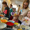 Anne Andrejko of Gloucester helps her daughters, Lucy Shea, 5, and Margot Shea, 3, select bowls during the Empty Bowl Dinner at Cruiseport yesterday. All proceeds from the event benefit the Open Door. Photo by Kate Glass/Gloucester Daily Times