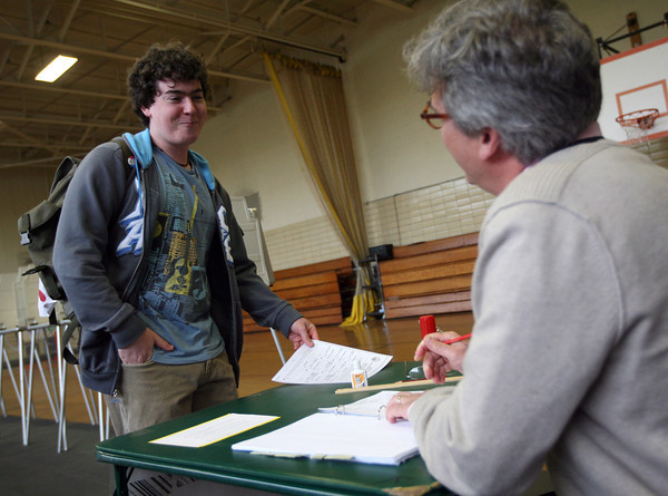 Manchester: Connof Hoff, 19, laughs as his father, Robert Hoff, asks for his name to check him off the list after voting in the Manchester election yesterday. Photo by Kate Glass/Gloucester Daily Times