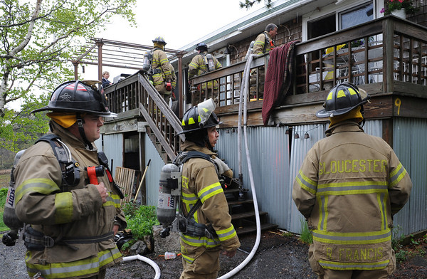 Gloucester:  Kelly Linehan on deck, talks with firefighters at 9 Whites Mt Rd Monday morning were a small fire was quickly knocked down. It's believed to have started by the washing machine in the laundry room. Desi Smith/Gloucester Daily Times.