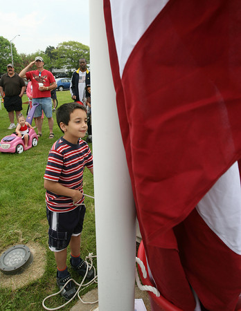 Nick Antonietti, 6, helps Joe Novello raise the American Flag at McKinnon Triangle for Gloucester's Memorial Day ceremony yesterday morning. Photo by Kate Glass/Gloucester Daily Times