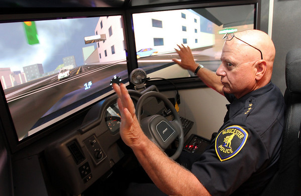 Gloucester Police Chief Michael Lane attempts to stop traffic while participating in a driving safety simulator program outside the Police Station. The simulator, which is presented by the Massachusetts Interlocal Insurance Association, is designed to reduce the risk of accidents and lower the city's insurance costs. Photo by Kate Glass/Gloucester Daily Times