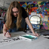 Alexis Chipperini, a student in Jacqueline Underwood's honors art class at Gloucester High School, paints a door inspired by Gloucester poet Charles Olson, which will be auctioned as part of the Gloucester Public School District Citywide Arts Festival, which is this Saturday. The doors will be on display at the Sawyer Free Library. Photo by Kate Glass/Gloucester Daily Times