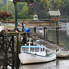 Manchester:  A man uses a pully to bring a empty barrall to the top of the dock at low tide next to Massconomo Park, Saturday morning. Desi Smith/Gloucester Daily Times.
