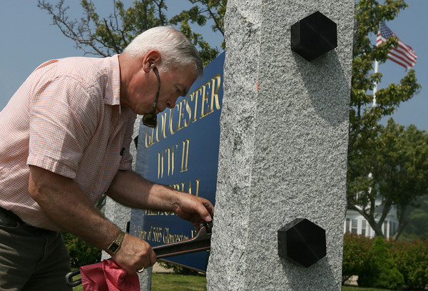 Gloucester: Roger Armstrong tightens the bolts holding a sign for the Gloucester World War II Memorial at Kent Circle. Armstrong designed the sign, which is made of Brazilian hardwood and fastened to granite pillars. Photo by Kate Glass/Gloucester Daily Times
