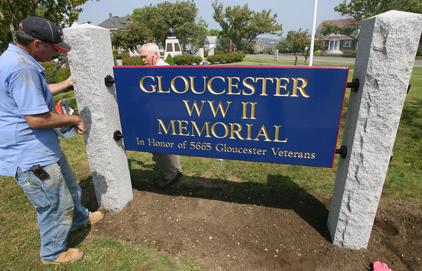Gloucester: James Kieran helps Roger Armstrong tighten the bolts on a new sign that Armstrong designed for Gloucester's World War II Memorial at Kent Circle. The sign was installed on Friday in preparation for today's Memorial Day ceremony. Photo by Kate Glass/Gloucester Daily Times