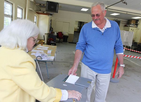 Phyllis Adison watches as Essex Town Moderator Rolf Madsen turns in his ballot during the Essex Election yesterday. Photo by Kate Glass/Gloucester Daily Times